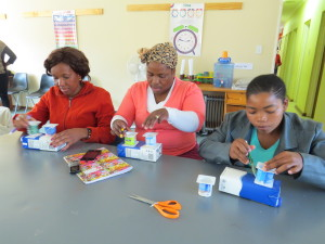 Toy Making by Caregivers on September 17, 2015 making paint brush holders from a milk cartoon and two yogurt containers.